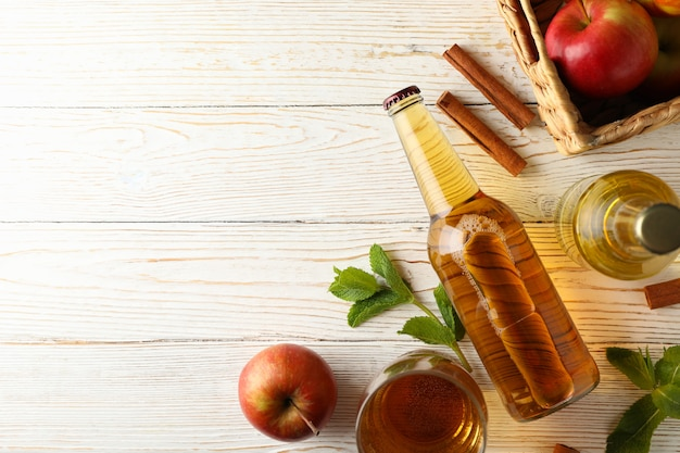 Composition with cider, cinnamon and apples on white wooden table