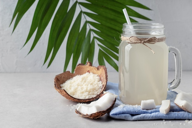 灰色のテーブル、空白スペースの石工の瓶にココナッツ水で構成