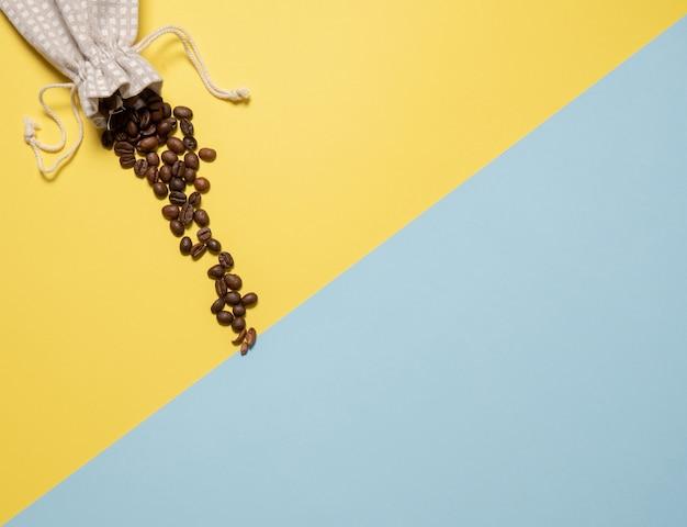 コーヒーとの組成。黄色と青の背景にコーヒーの粒がバッグからこぼれます。フラットレイ、上面図、コピースペース