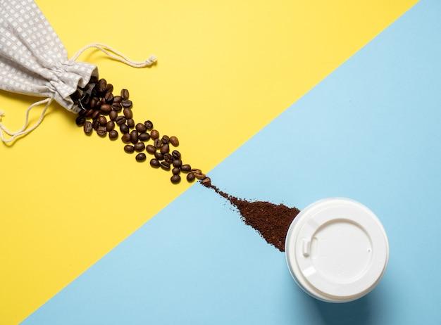 コーヒーとの組成。コーヒーの粒は黄色の背景でバッグからこぼれ出て、青い背景で挽いたコーヒーに変わります。フラットレイ、上面図、コピースペース