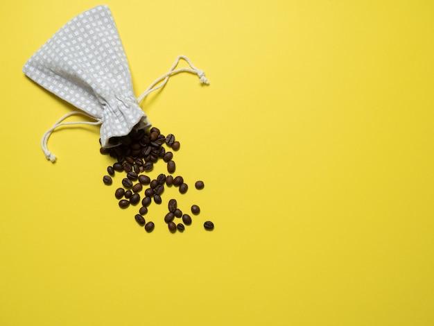 コーヒーとの組成。黄色の背景にコーヒーの粒がバッグからこぼれる