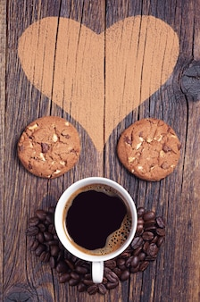 Composition with coffee, cookies and heart on the wooden background