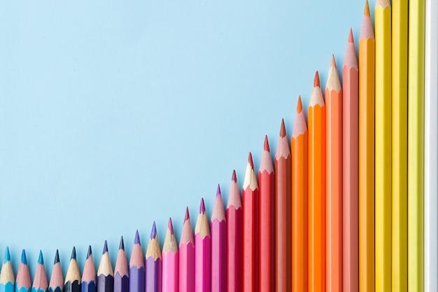 Композиция цветными карандашами на ярко-синем фоне. вид сверху. место для текста. фрейм