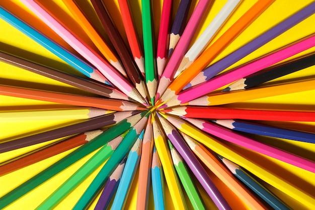 Композиция цветными карандашами на ярко-желтом фоне. крупный план. вид сверху