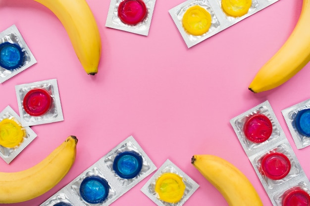 Composition with colorful condoms and bananas on pink surface