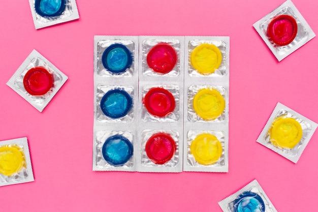밝은 분홍색 배경에 화려한 콘돔이 있는 구성. 안전한 섹스와 피임 개념. 평평한 평지, 평면도.