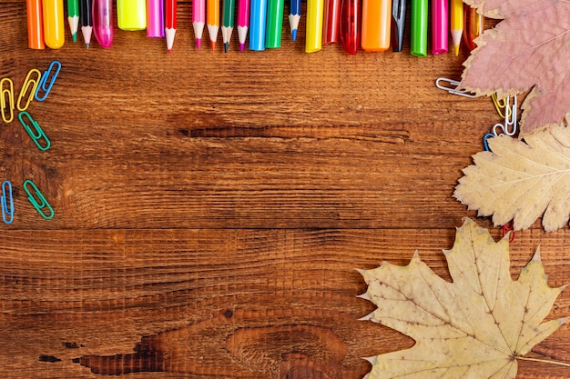 Композиция с копией пространства, цветной карандаш, осенние листья, маркер и ручка вернуться к концепции школы