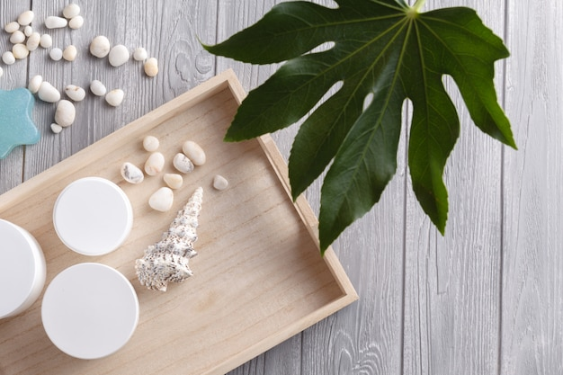 Composition with cosmetic products on white wood