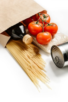 Composition with craft bag, spaghetti, tomatoes, rice, canned goods and olive oil isolated on a white wall.