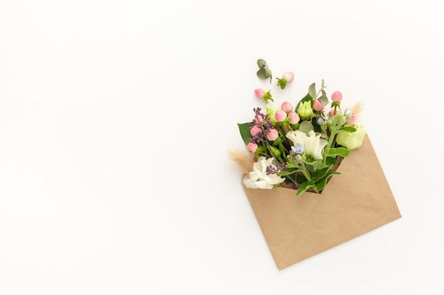 Композиция с крафтовым конвертом и нежными цветами
