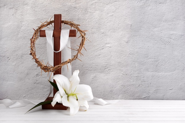 Composition with crown of thorns, wooden cross and lily on light background