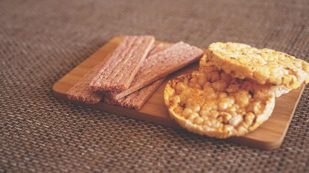 木製の背景にカリカリの餅を使った構成、側面図-ソフトフォーカス、健康食品