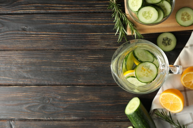 Composition with cucumber water in jug on wooden background, top view