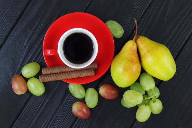 Composition with cup of coffee, grapes and ripe pears on the wood black background
