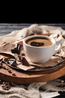 Composition with cup of coffee and served with coffee beans and chocolate