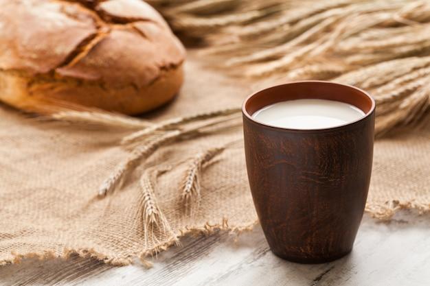 Композиция с чашкой молока, хлебом и колосьями ржи на мешковине.
