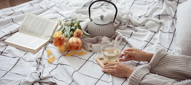 Composizione con una tazza di tè, una teiera, un mazzo di tulipani e un libro a letto