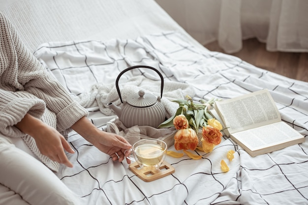 Composition with a cup of tea, a teapot, a bouquet of tulips and a book in bed
