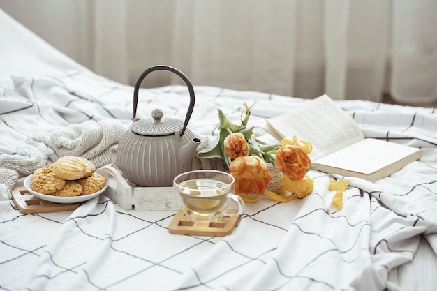 Composition with a cup of tea, a teapot, a bouquet of tulips and cookies in bed