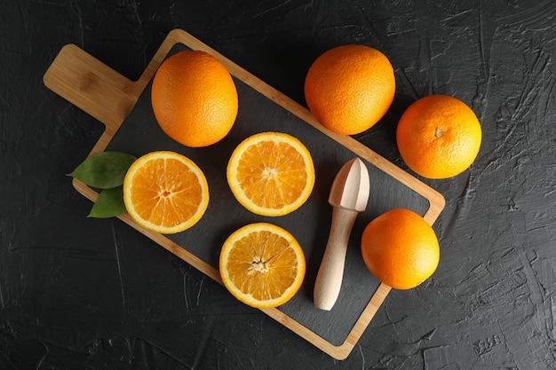 Композиция с разделочной доской, апельсинами и деревянной соковыжималкой. вид сверху, место для текста