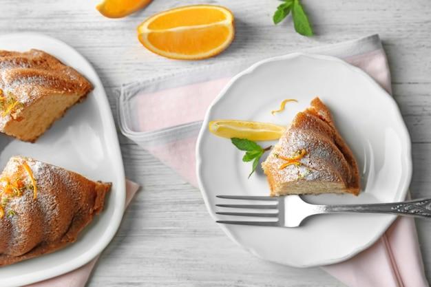 Композиция с вкусным цитрусовым пирогом на деревянном столе