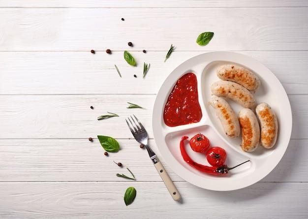 白い木製のテーブルの上においしい焼きソーセージとの構成
