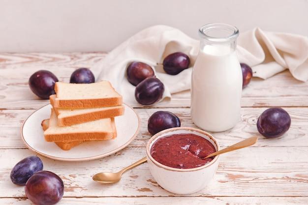 Композиция с вкусным домашним вареньем из сливы на деревянном столе
