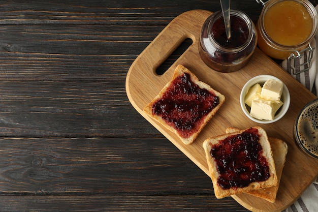 Composition with delicious toasts with jam on wood board, space for text