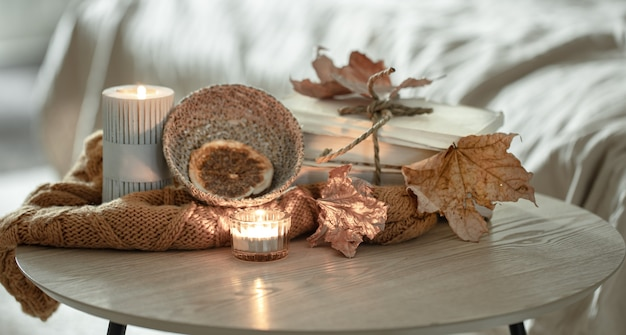 Composition with details of autumn decor on the table in the interior of the room.