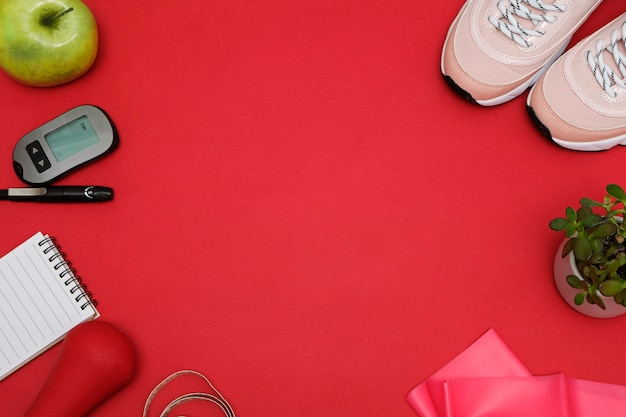 Composition with diet diabetes weight loss concept. sneakers, tape measure, glucometer on a red