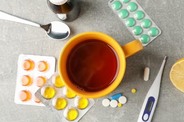 別の薬、温度計、医療バトル、一杯のお茶と灰色のテーブル上のレモンと組成。上面図