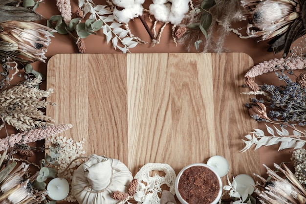 Composition with dried wildflowers and body care products on a wooden element in the center.