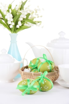 Composition with easter eggs in basket near teapot, cup and flowers bouquet