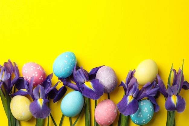 Composition with easter eggs and iris flowers on yellow surface