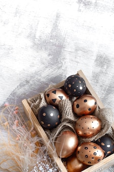 Composition with easter eggs painted in gold and black on light.