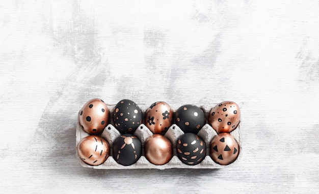 Composition with easter eggs painted in gold and black.
