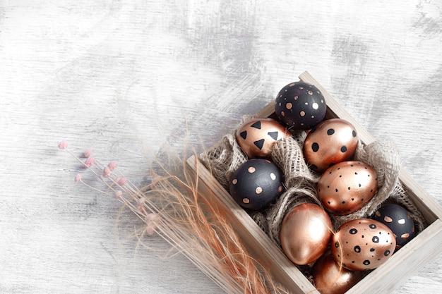 Composizione con uova di pasqua dipinte in oro e nero.