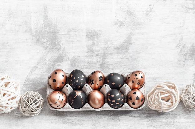 Композиция с пасхальными яйцами окрашены в золотой и черный на свет.