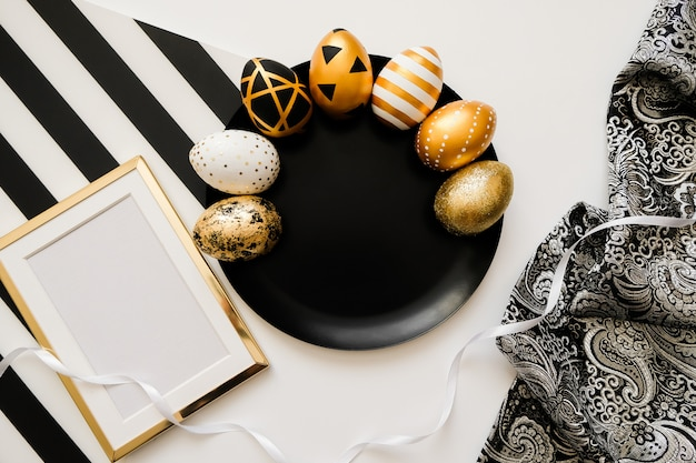 Composition with easter golden decorated eggs on black plate. trendy flat lay
