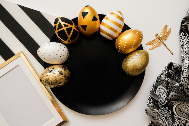 Composition with easter golden decorated eggs on black plate.