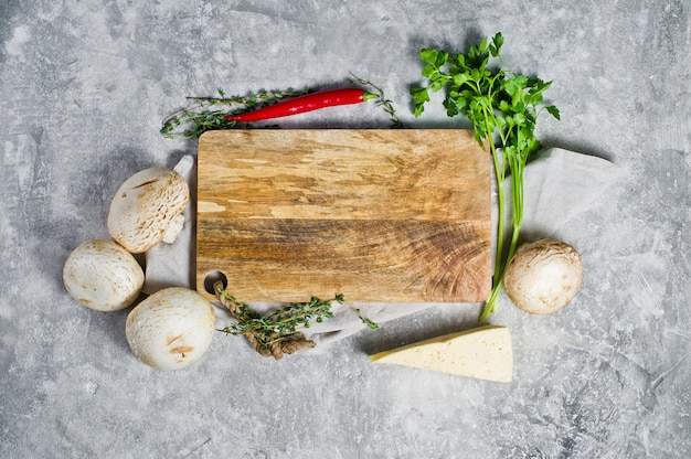 Composition with empty wooden board and vegetables on kitchen table