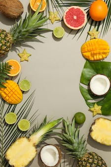 Composition with exotic fruits and palm leaves on grey background, space for text