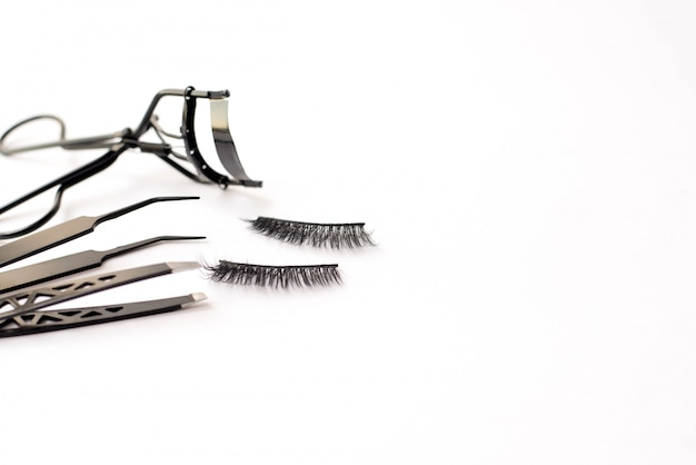 Composition with false eyelashes on white background