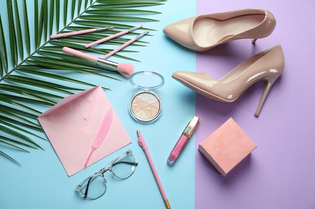 Композиция с женской обувью, косметикой и тропическим листом на цвете