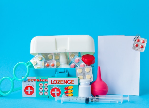 Composition with first aid kit on blue background