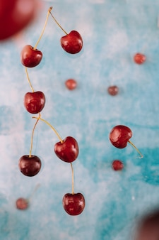 Composition with flying sweet red berries about levitation on blue background . levitating food, levitating berries