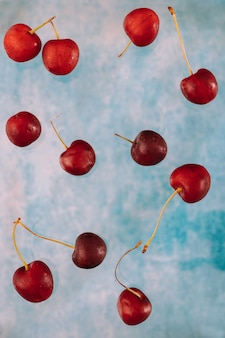 Composition with flying sweet red cherry about levitation on blue background . levitating food, levitating berries