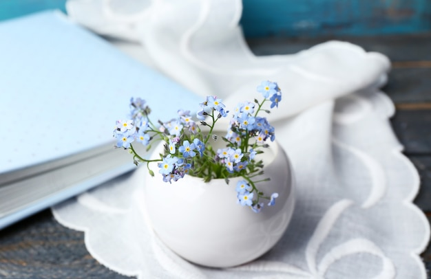 Composition with forget-me-nots flowers on wooden surface