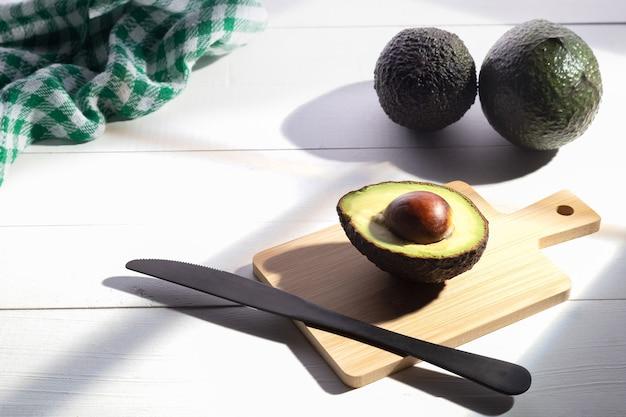 Композиция со свежими авокадо на белой деревянной основе.