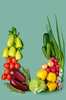 Композиция со свежими овощами на бледно-зеленом фоне